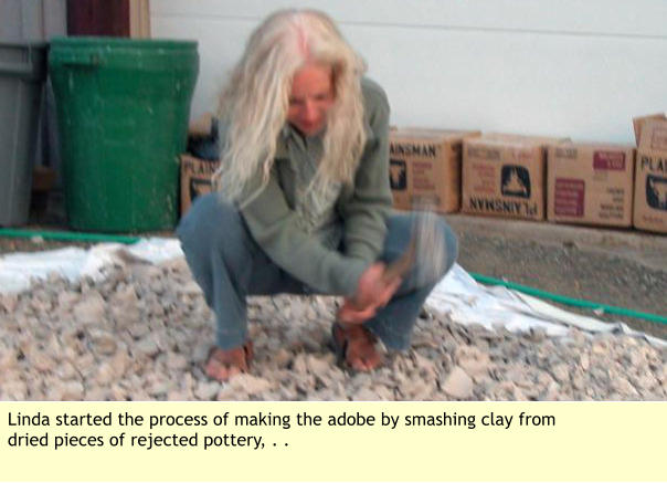 Linda started the process of making the adobe by smashing clay from dried pieces of rejected pottery, . .